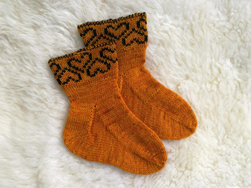 4 ply toe-up baby socks with hearts on the cuff.