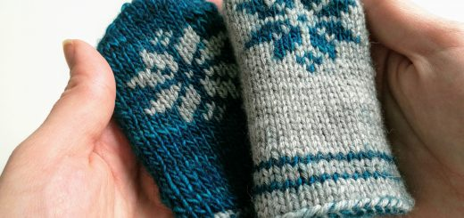 Thumbless baby mittens with a snowflake motif.